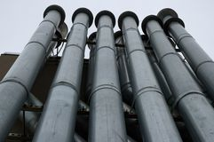 Tall Vent Pipes. Looking up some tall, industrial-looking vent pipes at the sky. New York City stock photo