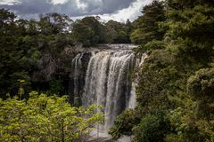 Tall Waterfall Framed By Bush Scenery. Tall waterfall after heavy rain, view of falls and landscape Stock Images