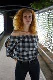 Tall, well-proportioned model-looking girl with red curly hair stands against the backdrop of glowing lights.  stock photography