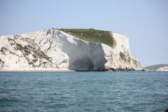 Tall white cliffs towering above a blue sea. White cliffs towering above a blue sea Stock Image