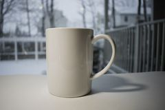 White Coffee Mug in front of snowy window. A tall white coffee mug in front of snow scene window on white surface Stock Images