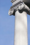 Tall white column. Tall vertical white column on a building, against a blue sky Stock Image