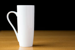 Tall white mug on a wood table Royalty Free Stock Image