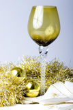 Tall wine glass Christmas New Year decorated table. Luxurious expensive tall wine glass on a beautiful Christmas New Year theme decorated table with golden royalty free stock image
