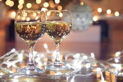Tall wine glasses with bubbly drink for celebration toast wrapped in a Christmas light. Decorated christmas tree in the background. Holiday concept stock image