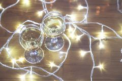Tall wine glasses with bubbly drink for celebration toast wrapped in a Christmas light. Close up. Tall wine glasses with bubbly drink for celebration toast stock photos