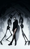Tall woman in black with black skeletons. In studio Stock Photo