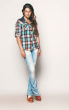 Tall woman in check shirt and blue jeans. In studio Royalty Free Stock Photography
