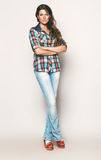 Tall woman in check shirt and jeans. In studio Royalty Free Stock Photos