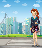 A tall woman standing near the pedestrian lane Stock Image