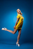 Tall woman in yellow sexy dress jump on blue Royalty Free Stock Photos