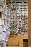 Tall wooden shelves with papers, all over the walls entirely, a document repository, a search ladder on the upper shelves stock image