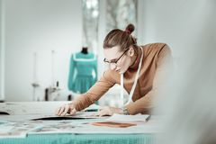 Tall young designer from a fashion school in eyeglasses looking serious. Busy time. Handsome young designer from a fashion school wearing eyeglasses looking stock photography
