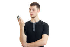 Tall young strong guy stands up straight and holding a Clipper to shave. Isolated on white background Stock Photo