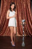 Tall young woman holding hookah. Stock Images
