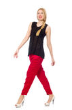 The tall young woman in red pants isolated on white Stock Photo