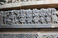 Talla de la pared del templo de Hoysaleswara de los demonios que marchan para la guerra de la lucha Imagenes de archivo