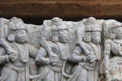 Talla de la pared del templo de Hoysaleswara de los guerreros que marchan con la armadura Fotografía de archivo