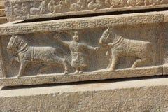 Talla del templo de Hampi Vittala de un hombre que controla dos caballos que marchan Fotografía de archivo libre de regalías