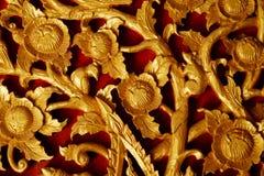 Talla local de oro de pintura de la flor y del ornamento del fondo rojo de madera con diseño tailandés del estilo Imagen de archivo