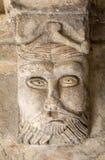 Talla Románica de un capital extraño de la cabeza o de la cara c12th en claustros de la abadía de Montmajour cerca de Arles Fotos de archivo