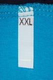 Talla XXL de la escritura de la etiqueta en el paño azul. fotografía de archivo