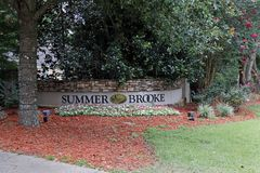 Summer Brooke Neighborhood Sign Wall with Foliage Outside. Tallahassee, FL, USA - July 14, 2018: Neighborhood sign of Summer Brooke community in northeast stock photography