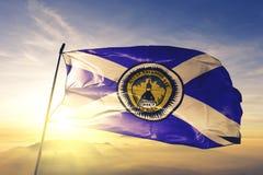 Tallahassee-Stadthauptstadt von Florida des Flaggentextilstoffgewebes Vereinigter Staaten, das auf den Spitzensonnenaufgangnebeln stockbild