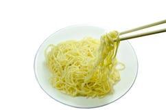 Tallarines amarillos vegetarianos que escogen en palillos en la placa fotos de archivo libres de regalías
