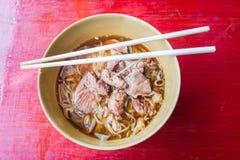 Tallarines asiáticos con cerdo guisado en el cuenco imagen de archivo