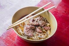Tallarines asiáticos con cerdo guisado en el cuenco imagen de archivo libre de regalías