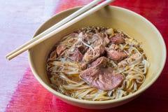 Tallarines asiáticos con cerdo guisado en el cuenco fotos de archivo