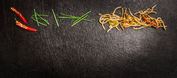 Tallarines asiáticos con las cebolletas verdes y el chile rojo en el fondo oscuro de la pizarra, visión superior, bandera Imágenes de archivo libres de regalías