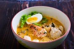 Tallarines asiáticos con los mariscos y el huevo en la sopa del tomyum fotos de archivo
