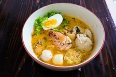 Tallarines asiáticos con los mariscos y el huevo en la sopa del tomyum foto de archivo