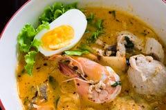 Tallarines asiáticos con los mariscos y el huevo en la sopa del tomyum fotografía de archivo libre de regalías