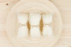 Tallarines asiáticos crudos del celofán de las gavillas en la placa en el tablero de madera beige, visión superior Imagenes de archivo