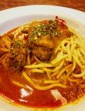 Tallarines calientes y picantes del pollo del rendang en la tabla Imagenes de archivo