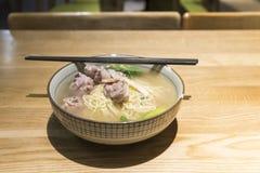 tallarines chinos con la sopa del cartílago del cerdo en el fondo de madera de la tabla Imagen de archivo libre de regalías