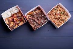 Tallarines con cerdo y verduras en caja para llevar en la tabla de madera fotografía de archivo