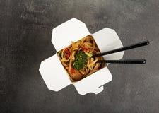 Tallarines con la carne y las verduras en wok de la caja, en superficie gris imagen de archivo libre de regalías
