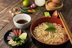 Tallarines con la salsa o el shoyu e ingrediente en backgro de madera de la tabla Fotografía de archivo