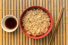 Tallarines con shoyu o la salsa en el backgroound de bambú o de madera Fotos de archivo libres de regalías