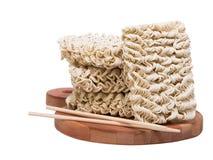Tallarines crudos inmediatos de los Ramen en el tablón de madera 3/4 con los palillos Imagen de archivo