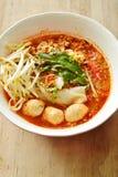 Tallarines de arroz con la bola del cerdo en la sopa picante de tom yum que remata el brote de haba fresca en el cuenco Foto de archivo libre de regalías