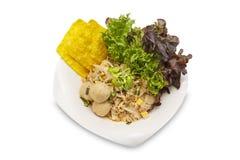 Tallarines de arroz frescos sofritos con las bolas picaditas del cerdo y de carne en fondo blanco aislado Foto de archivo libre de regalías