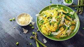 Tallarines de las pastas con el espárrago, los guisantes, las habas y el queso parmesano en el top Alimento sano fotografía de archivo libre de regalías