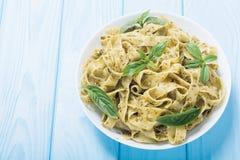 Tallarines de las pastas con el fondo italiano de la comida del pesto verde de la salsa imagenes de archivo