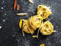 Tallarines de las pastas del Fettuccine adornados con los pedazos de paprika rojo y de harina fría del pimienta y blanca imagen de archivo libre de regalías