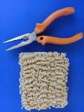 Tallarines de Ramen al lado de los alicates - concepto para fijar cualquier cosa usando los tallarines - fondo azul foto de archivo